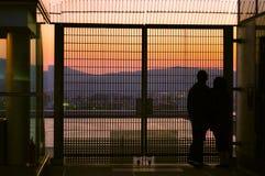 Paar die op de zonsondergang letten door een omheining royalty-vrije stock afbeeldingen