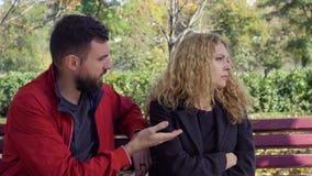 Paar die op een bank in een park debatteren stock footage