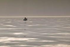 Paar die op een kleine boot op een mistige dag vissen Stock Afbeeldingen