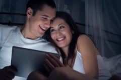 Paar die op een Video op Hun Tabletcomputer letten Stock Afbeeldingen