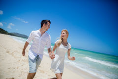 Paar die op een zandig strand lopen Stock Foto