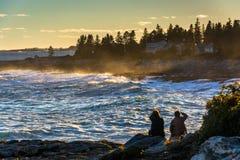 Paar die op grote golvenneerstorting op rotsen letten bij zonsondergang, in Pemaqui royalty-vrije stock foto's