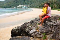 Paar die op het overzees letten terwijl status op een rots Stock Fotografie