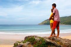 Paar die op het overzees letten terwijl status op een rots Royalty-vrije Stock Afbeeldingen