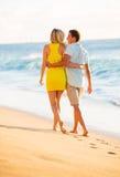 Paar die op het strand bij Zonsondergang, Romantische Vakantie lopen Stock Fotografie