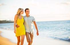 Paar die op het strand bij Zonsondergang, Romantische Vakantie lopen Stock Afbeeldingen
