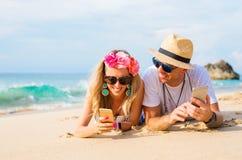 Paar die op het strand liggen en mobiele telefoons met behulp van stock foto