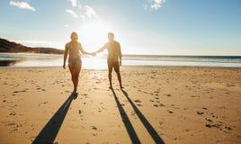 Paar die op het strand samen bij zonsondergang lopen Royalty-vrije Stock Afbeeldingen