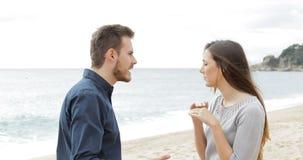Paar die op het strand verdelen stock video