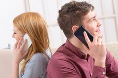 Paar die op hun smartphones spreken royalty-vrije stock afbeeldingen