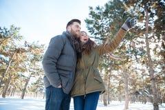 Paar die op iets in de winterpark kijken Stock Foto