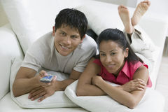 Paar die op Laag met Afstandsbediening liggen Stock Afbeelding