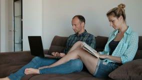 Paar die op laagzitting in Internet met laptop op vakantie liggen stock video