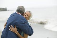 Paar die op middelbare leeftijd bij strand omhelzen stock afbeeldingen