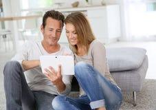 Paar die op middelbare leeftijd tablet thuis gebruiken stock foto's