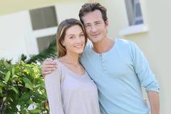 Paar die op middelbare leeftijd zich voor huis bevinden Royalty-vrije Stock Foto's
