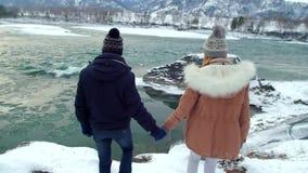 Paar die op sneeuw door de winterlandschap lopen stock footage