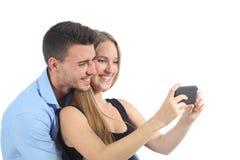 Paar die op sociale media op de slimme telefoon letten Stock Foto's