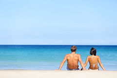Paar die op strandzitting in zand op zee kijken Stock Foto