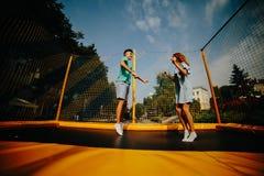 Paar die op trampoline in het park springen Stock Afbeeldingen