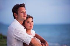 Paar die op tropische zonsondergang letten stock foto