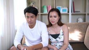Paar die op TV op bank letten stock video