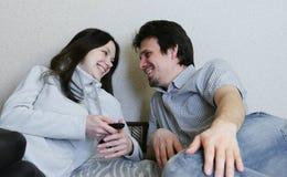 Paar die op TV letten liggend op de laag De man en een vrouw bekijken elkaar en glimlach stock foto