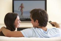 Paar die op TV Met groot scherm thuis letten Stock Foto's