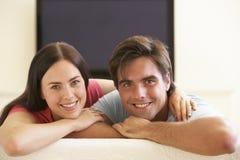 Paar die op TV Met groot scherm thuis letten Stock Foto