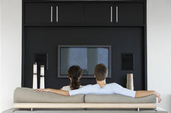 Paar die op TV samen in Woonkamer letten Stock Foto's