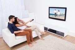 Paar die op TV in woonkamer letten Stock Afbeelding