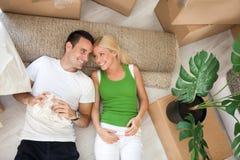 Paar die op vloer in nieuw huis liggen Stock Foto's