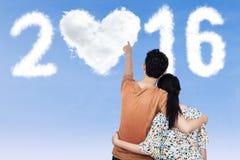 Paar die op wolken gestalte gegeven nummer 2016 richten Royalty-vrije Stock Foto's