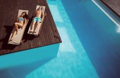 Paar die op zonlanterfanters door zwembad rusten Stock Foto's