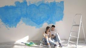 Paar die over binnenlands ontwerp op de achtergrond van geschilderde muur spreken stock videobeelden