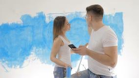 Paar die over binnenlands ontwerp op de achtergrond van geschilderde muur spreken stock footage