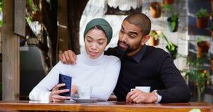 Paar die over mobiele telefoon in cafetaria 4k bespreken stock footage
