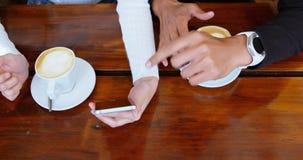 Paar die over mobiele telefoon in cafetaria 4k bespreken stock videobeelden