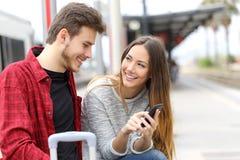 Paar die over online inhoud in een telefoon spreken royalty-vrije stock afbeeldingen