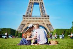 Paar die picknick hebben dichtbij de toren van Eiffel in Parijs stock afbeelding