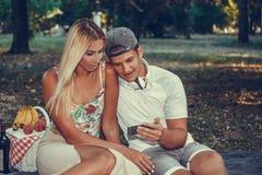 Paar die picknick van dag genieten en aan de muziek luisteren stock foto's