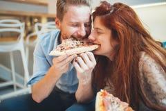 Paar die pizza en het eten delen royalty-vrije stock afbeeldingen