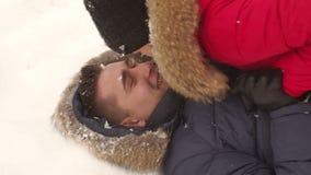 Paar die pret in de winter hebben, liggen zij op sneeuw stock video