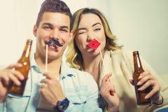 Paar die pret hebben die kunstmatige snor en lippenstok houden Stock Foto