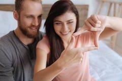 Paar die pret hebben en gezichten met handen ontwerpen Royalty-vrije Stock Foto's