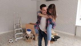 Paar die pret hebben en het bewegen in een nieuw huis vieren zich housewarming stock video