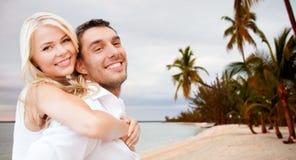 Paar die pret hebben en op strand koesteren Stock Foto's