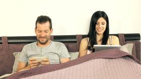 Paar die pret met elektronische gadgets hebben stock videobeelden