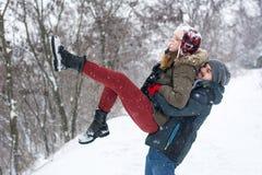 Paar die pret in sneeuw behandeld park hebben stock foto's