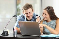 Paar die producten online kopen vergelijken met laptop royalty-vrije stock fotografie